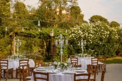 Wedding-tables-set-up-ouside-with-white-candles-and-roses_